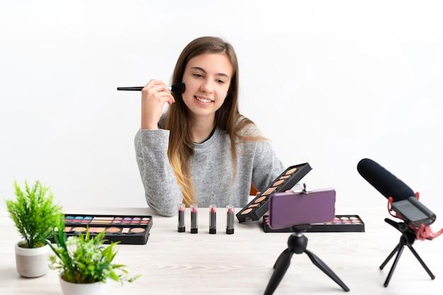 Donna che fa il blog di tutorial di trucco cosmetico con vernici per il trucco guardando la telecamera condividendoli sui social media online in diretta