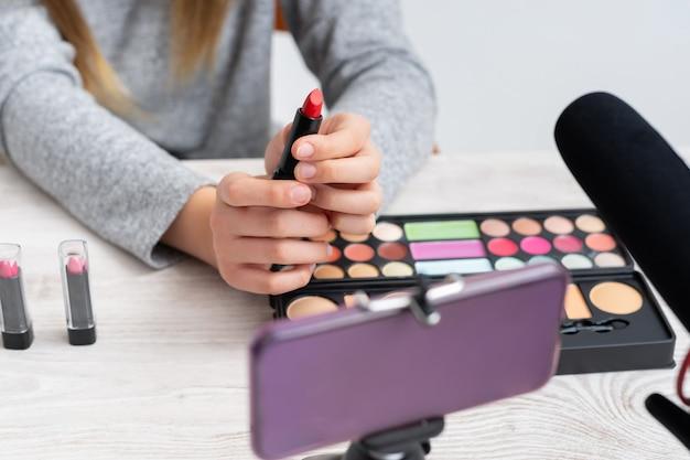 Donna che fa il blog tutorial di trucco cosmetico con vernici per il trucco condividendole sui social media in diretta su internet online
