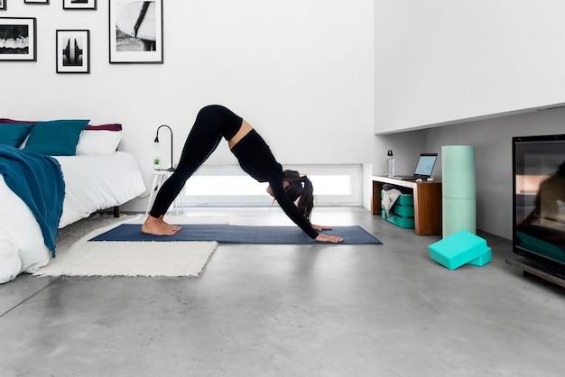 Donna che fa cane con la testa in giù utilizzando il programma di formazione yoga online nel computer portatile a casa