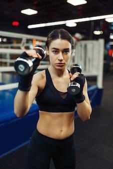 Donna che fa esercizio con manubri, box training, ring di pugilato sullo sfondo. pugile femminile in palestra, kickboxer ragazza nel club sportivo, allenamento kickboxing
