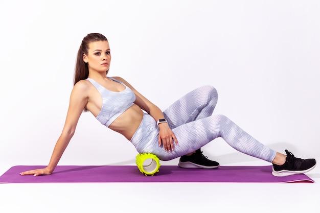 Donna che fa esercizi sdraiata sul tappetino, usando il rullo fitness per massaggiare e alleviare la tensione dalla schiena