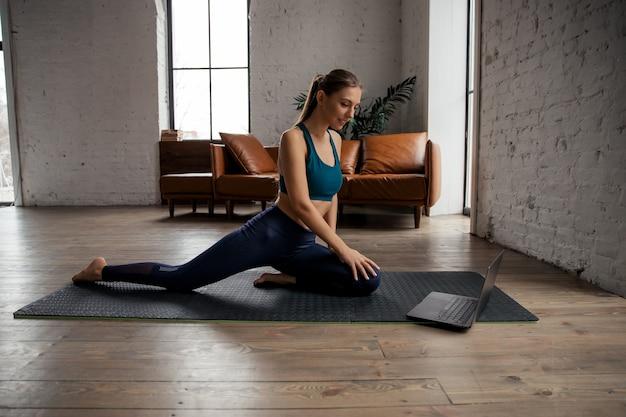Donna che fa esercizi di fitness sulla stuoia di fronte al computer portatile a casa. benessere e concetto di stile di vita sano. . foto di alta qualità