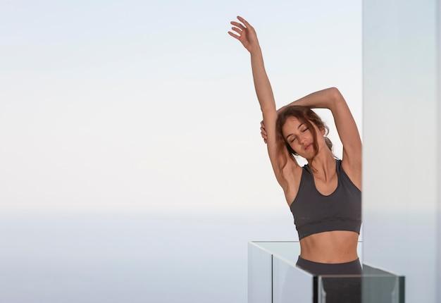 Donna che fa forma fisica a casa sul balcone
