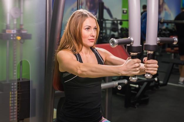 Donna che fa allenamento fitness su una macchina a farfalla con pesi in una palestra