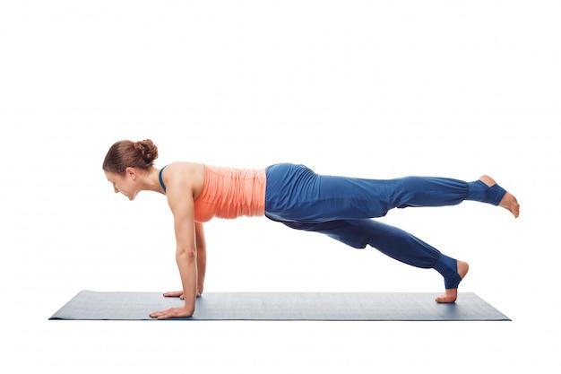 Donna che fa hatha yoga asana utthita chaturanga dandasana