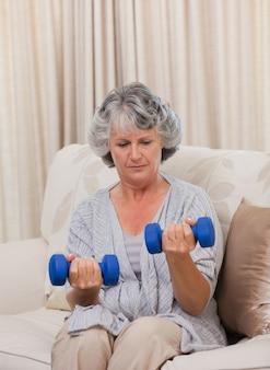 Donna facendo i suoi esercizi sul suo divano