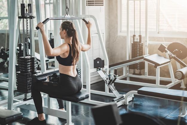 La donna che fa la tirata del lat abbassa l'esercizio nella palestra di forma fisica