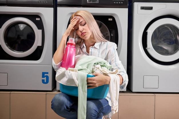 Donna che fa il bucato, espressione triste e depressa, cattivo umore dopo una dura giornata di lavoro, in lavatrice. personale stanco ed esausto