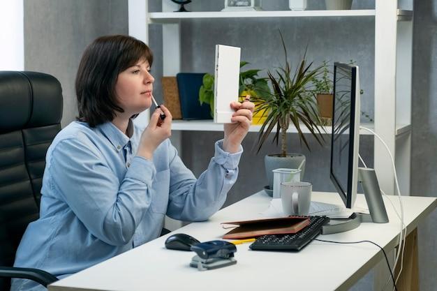 Donna che fa trucco e si pavoneggia sul posto di lavoro. la ragazza dipinge le labbra al lavoro in un ufficio privato.