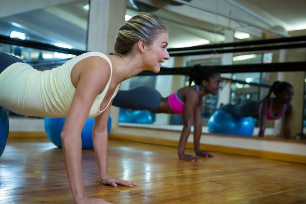 Donna che fa esercizi di pilates sulla palla fitness con allenatore in studio fitness
