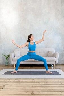 Donna che fa sport a casa allenamento che allunga nello yoga stando in piedi