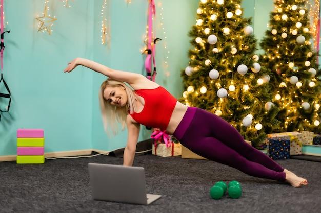 Donna che fa sport online sul computer portatile durante le vacanze di natale. concetto di allenamento di capodanno per lo stretching e lo yoga. formazione online nella pandemia di covid.
