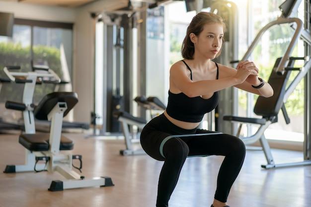Donna che fa squat con fascia elastica in palestra