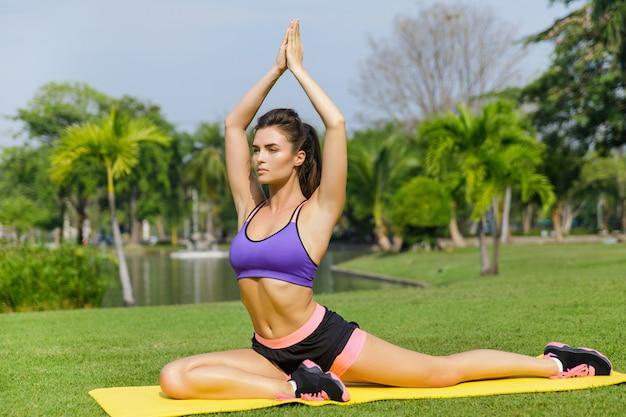 La donna che fa l'allungamento si esercita sulla stuoia di forma fisica