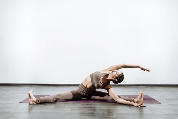 Donna che fa yoga sul tappeto facendo stretching