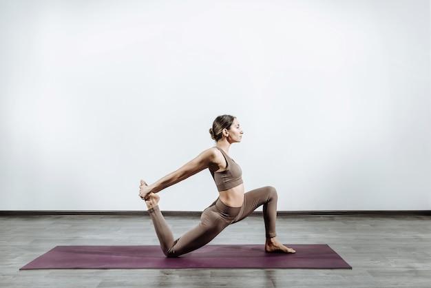 Donna che fa yoga sul tappeto a casa