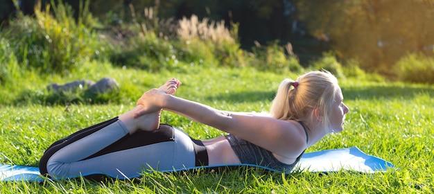 Donna che fa yoga in un parco cittadino sul fiume in estate.