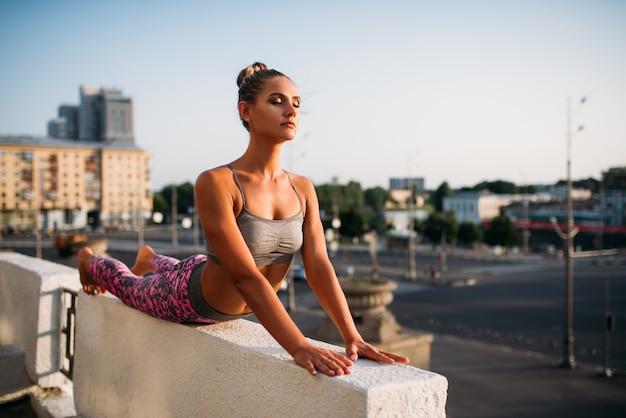 Donna che fa esercizio di yoga, città