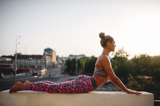 Donna che fa esercizio di yoga, città Foto Premium