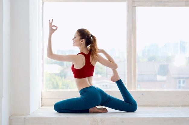 Donna che fa esercizio di yoga vicino al rilassamento della finestra