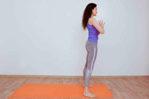 Donna che fa esercizio di yoga sulla stuoia arancione, stretching.