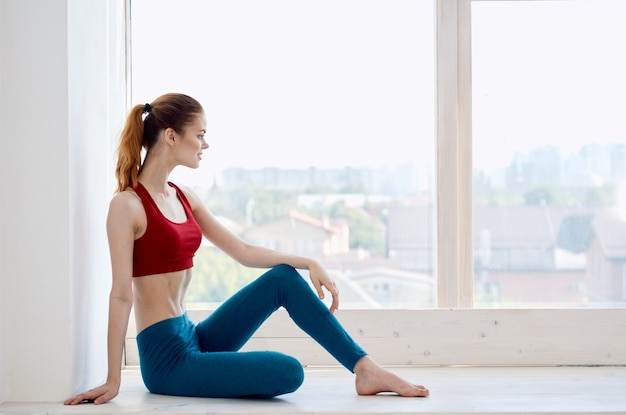 Donna che fa esercizi di yoga vicino all'asana di energia della finestra