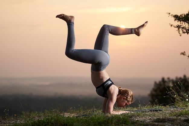 Donna facendo esercizi di yoga all'aperto al tramonto