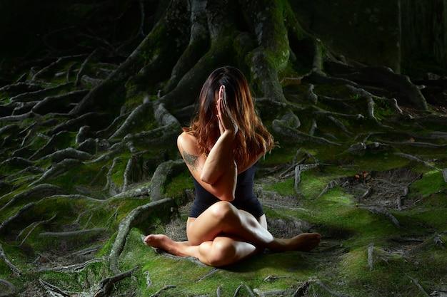Donna che fa yoga nella foresta meditando in silenzio