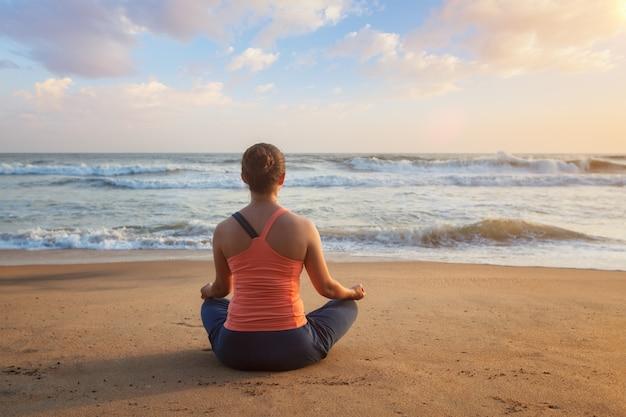 Donna che fa yoga oudoors di posa del loto in spiaggia