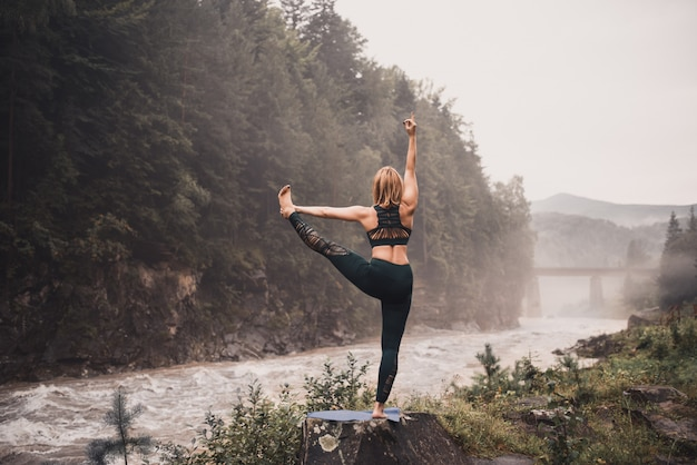 Donna che fa yoga su una riva del fiume