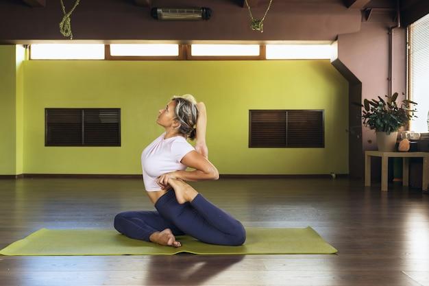 Donna che fa yoga seduta su un tappetino esegue l'esercizio eka pada rajakapotasana un maiale complicato
