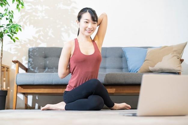 Una donna che fa yoga mentre guarda lo schermo del computer nella stanza