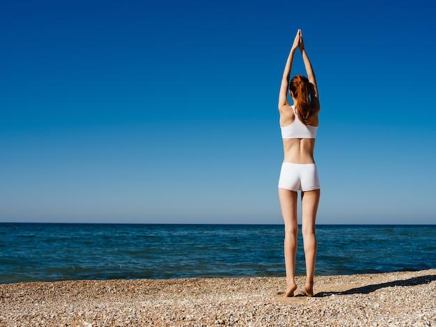 Donna che fa yoga in costume da bagno bianco sulla spiaggia estiva. foto di alta qualità