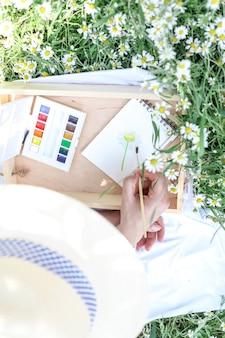 Donna che disegna con l'acquerello all'aperto