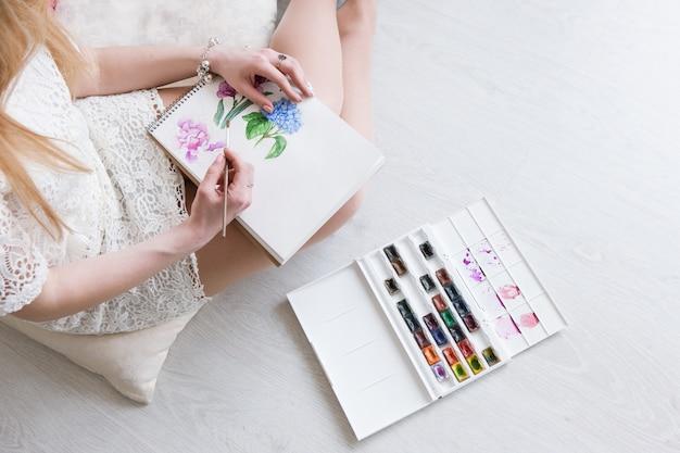 La donna disegna in vista dall'alto dell'acquerello il lavoro del pittore con lo schizzo. opere d'arte colorate di fiori su carta bianca. vernice dell'artista con tavolozza e pennello.