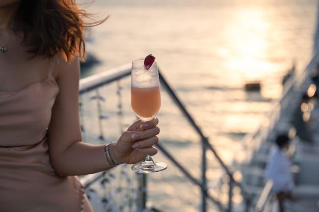 Donna in vestito che tiene cocktail misto sul bar sul tetto della crociera alla sera