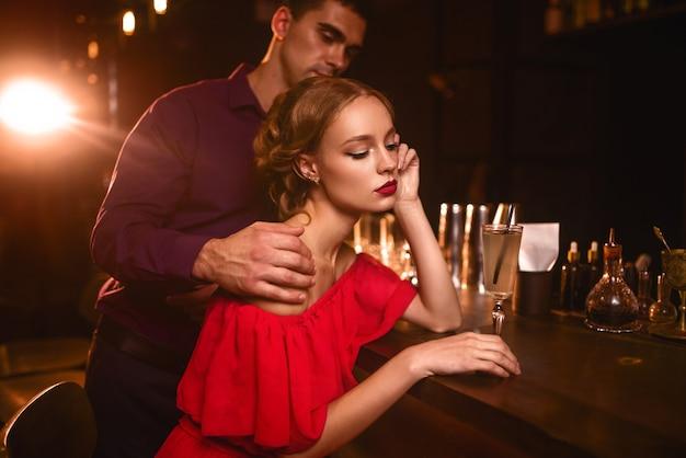 Donna in abito e uomo dietro il bancone del bar, flirtare