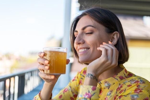 Donna in vestito in caffè estivo gustando un bicchiere di birra kombucha fresco