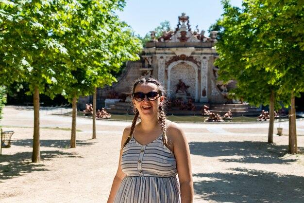Donna in abito e occhiali da sole passeggiando per i giardini del palazzo di granja de san idelfonso.