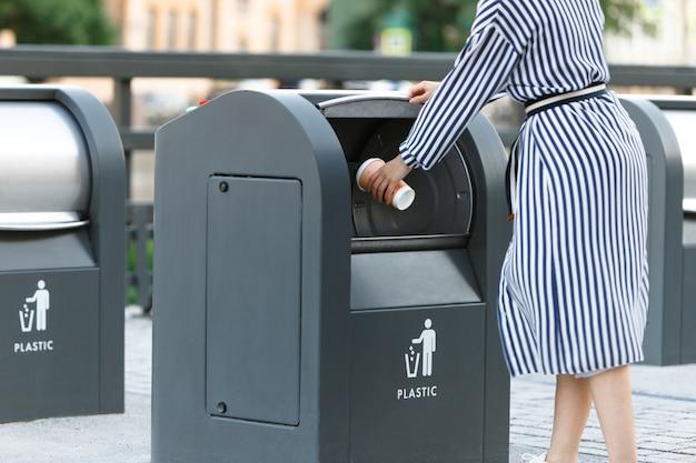 Donna in vestito che getta la tazza di caffè vuota in recipiente di riciclaggio, fine in su