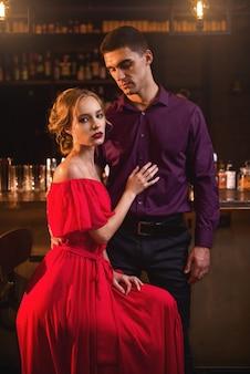 Donna in vestito con il suo uomo contro il bancone del bar