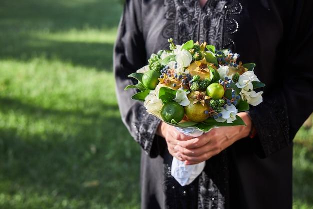 La donna vestita di abaya è in piedi con un mazzo di fiori e frutti nelle sue mani