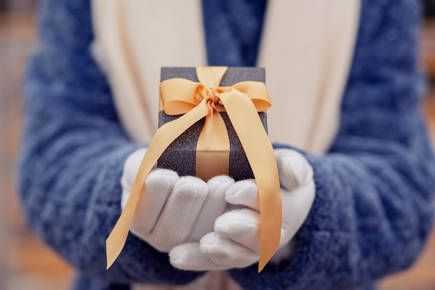 Donna vestita con un cappotto invernale blu che tiene una scatola regalo con un nastro di seta per strada