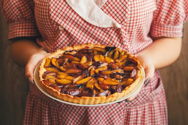 La donna vestita con un vestito tiene in mano un bel piatto con prugne o crostata di prugne.