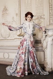 Donna vestita con un abito nel palazzo in posa accanto al camino