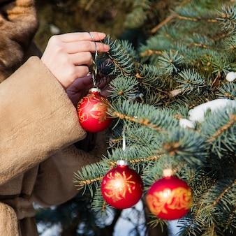 La donna si è vestita in una pelliccia che appende le decorazioni di natale su abete