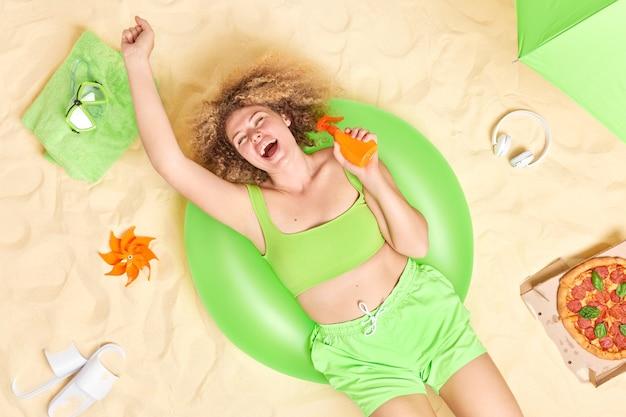 Donna vestita di verde in alto e pantaloncini tiene una bottiglia di crema solare pone sul nuoto gonfiato trascorre il tempo libero in spiaggia sabbiosa mangia la pizza ha una giornata pigra