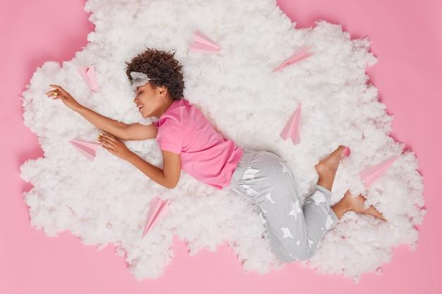 La donna vestita con indumenti da notte vede piacevoli sogni in posa su una soffice nuvola bianca con aeroplanini di carta intorno al rosa