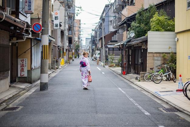 Donna vestita in costume tradizionale giapponese che cammina sotto i tori gate al santuario fushimiinari kyoto japan