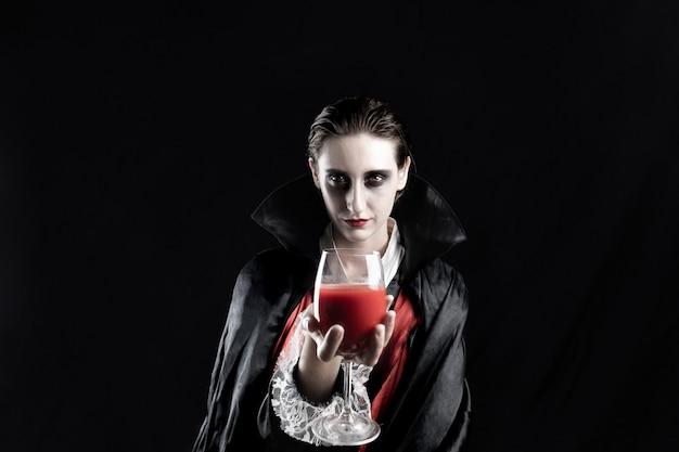 Donna vestita come un vampiro per halloween tenendo un bicchiere di bevanda rossa. studio girato in luci drammatiche di una giovane donna in costume di dracula su sfondo nero
